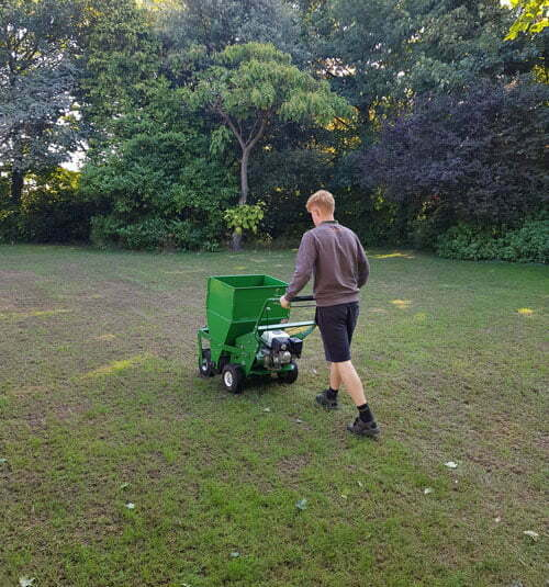 lawn technician preparing lawn for lawn dressing