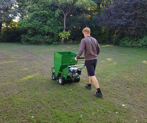 UK Lawn Care Association technician applying top dressing